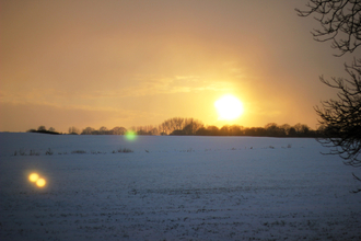 Snowy sunset over a field, photo by Vic Hill
