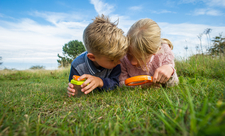 Children outdoors with magnifying glass, photo by Matthew Roberts