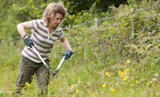 Volunteer clearing brambles, photo by Ross Hoddinott/2020VISION