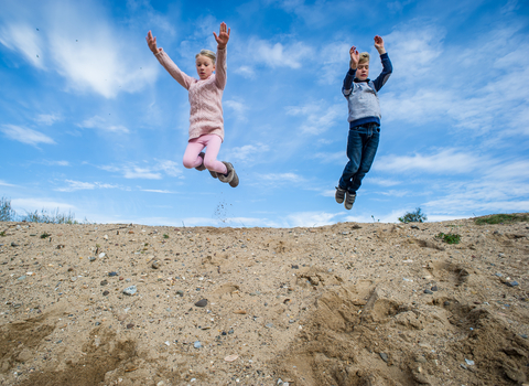 Children playing and jumping outdoors, photo by Matthew Roberts